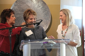Suzanne Cisneros (Founding Member) and Kathy Elliott (Co-Chair Grants Committee) present a necklace by local jeweler Lawrence Baca to Founder Susan Priem.